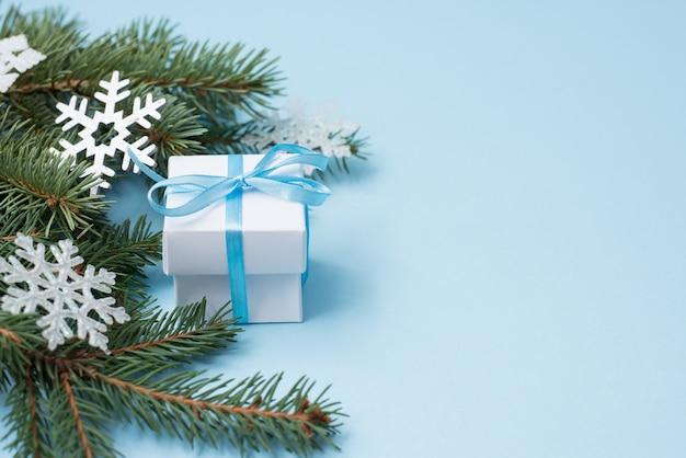 青色の背景、コピースペースに白いクリスマスギフトボックス。緑の木と雪の冬のフラットレイアウト