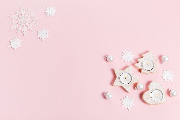 White christmas holiday composition. festive creative white pattern, xmas decor holiday ball with candles, snowflakes on pink background. flat lay, top view