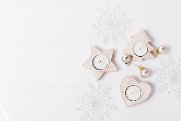 White christmas holiday composition. festive creative white pattern, xmas decor holiday ball with candles, snowflakes on white background. flat lay, top view