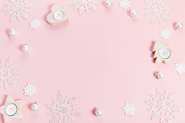 White christmas holiday composition. festive creative white pattern, xmas decor holiday ball with snowflakes on pink background. flat lay, top view