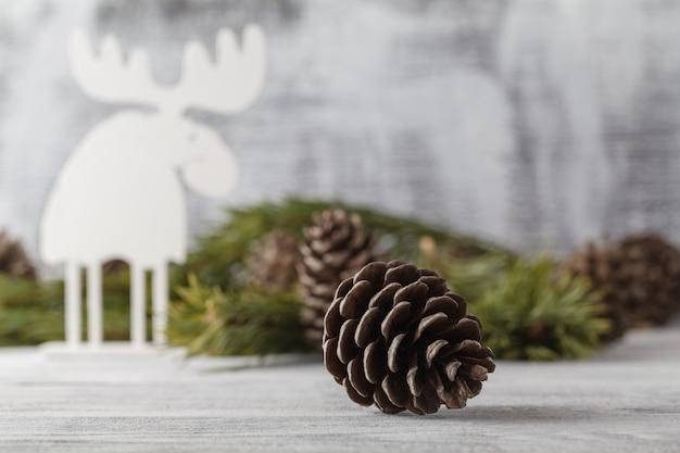 ホワイトクリスマスの飾り、素朴な木のテーブルにクリスマスツリー。メリークリスマスカード。冬の休日のテーマ。明けましておめでとうございます。