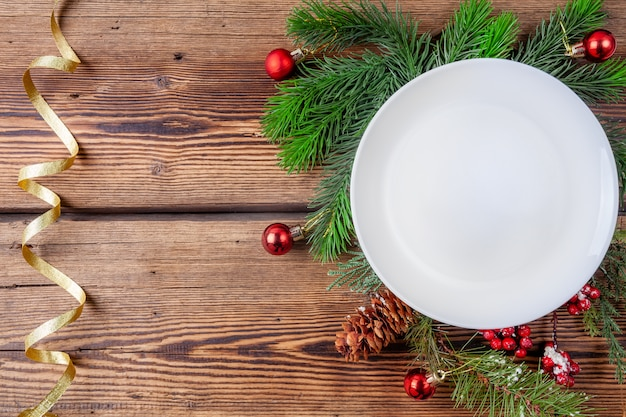 White christmas plate with pine branches with christmas decorations on wooden background with golden ribbon