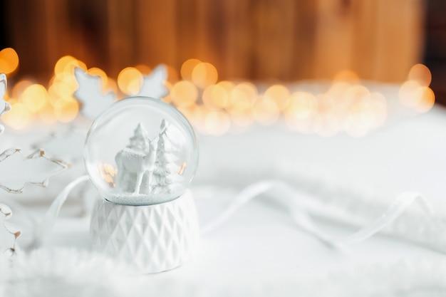 クリスマスの装飾が施されたテーブルの上の白いクリスマスのスノードーム。
