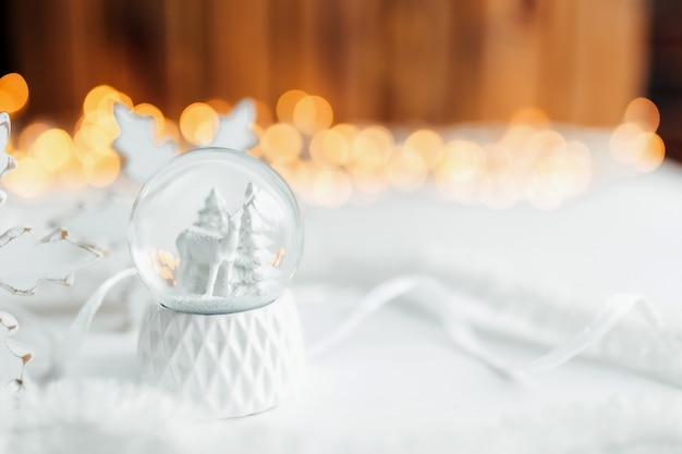White christmas snow globe on a table with christmas decorations.
