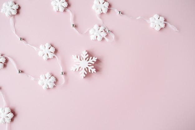 ピンクの背景に白いクリスマスの雪片の装飾。クリスマスの壁紙。