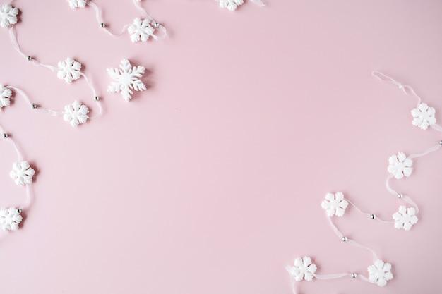 ピンクの白いクリスマスの雪片の装飾。クリスマス