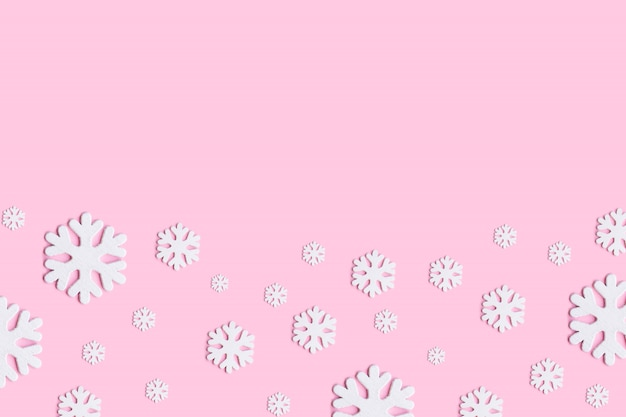White christmas snowflakes decoration on pink background.