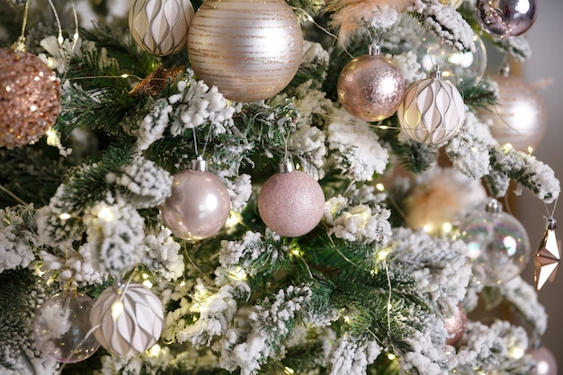 緑の雪に覆われたモミの枝にぶら下がっている白いクリスマスのおもちゃ