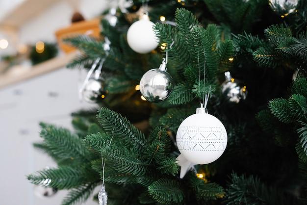 Белые елочные игрушки на елке крупным планом