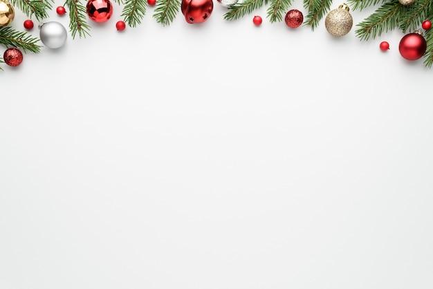 モミの枝や装飾と白いクリスマスツリーの背景。お祝いのテキスト用のコピースペースを備えたハッピーホリデーフレーム。上面図、フラットレイ