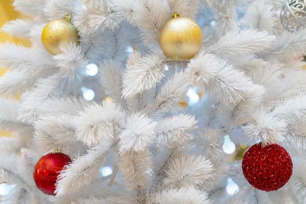 Белая елка, украшенная мини-огоньками, красными и золотыми шарами