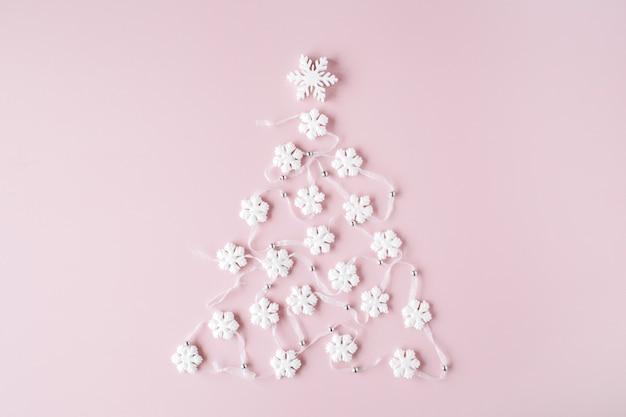 ピンクの背景に白いクリスマスツリーの装飾。クリスマスの壁紙。