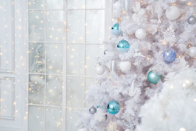 White christmas tree with beautiful balls, toys in turquoise, white and silver colors.
