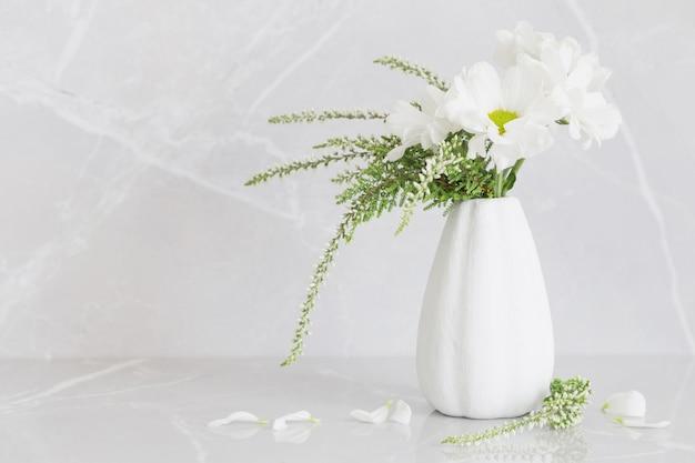 Белые хризантемы в вазе на сером мраморном фоне