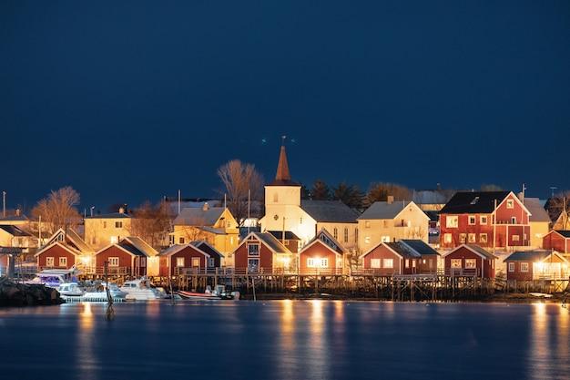 White church in fishing village on coastline at night, lofoten, norway