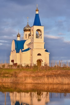 White church with blue roof on shore of lake, the church at sunset