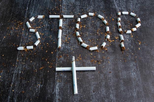 흰색 담배는 묘비 십자가 형태로 접혀 있습니다. 흐릿한 정지 신호. 개념: 흡연으로 인한 피해, 금연