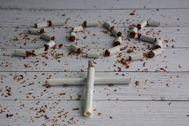 흰색 담배는 묘비 십자가 형태로 접혀 있습니다. 배경에는 흐릿한 sos 표시가 있습니다. 개념: 흡연으로 인한 피해. 흡연으로부터 자신을 구하십시오