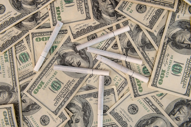 White cigarettes lying on the dollar bills. concept of financial cost of smoking. Premium Photo