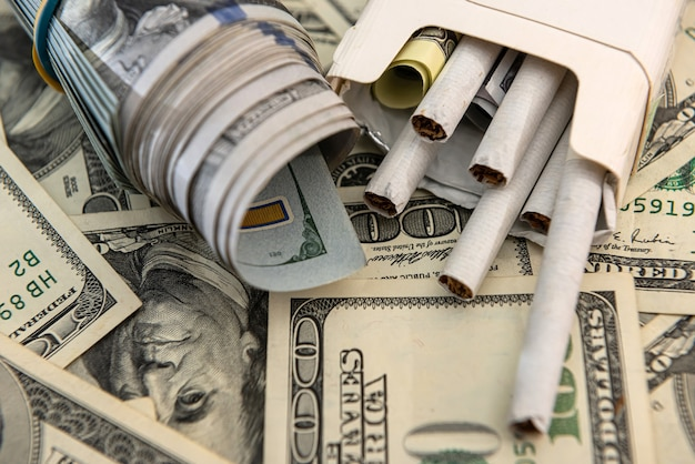 White cigarettes lying on the dollar bills. concept of financial cost of smoking.
