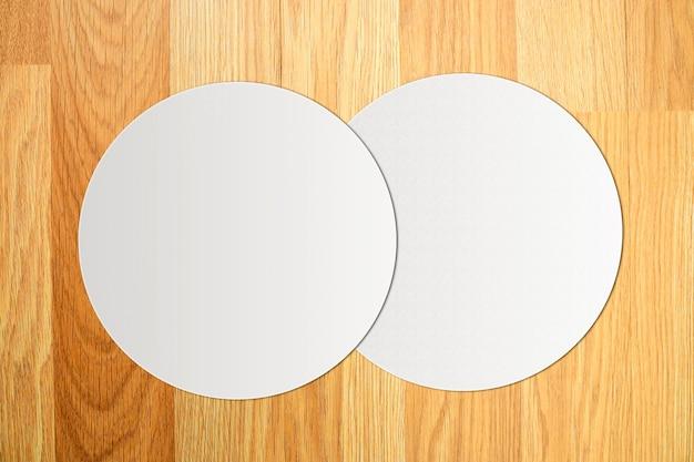 ヴィンテージの茶色の木製の背景に白い円の紙。上面図