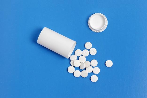 Таблетки белого круга и пластиковая бутылка для таблеток на синем фоне