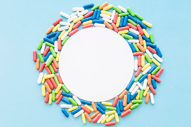 White circular blank frame decorated with colorful candies on blue background