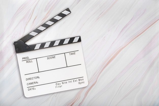 White clapboard on marble background. open white clapper board on marble texture. top view