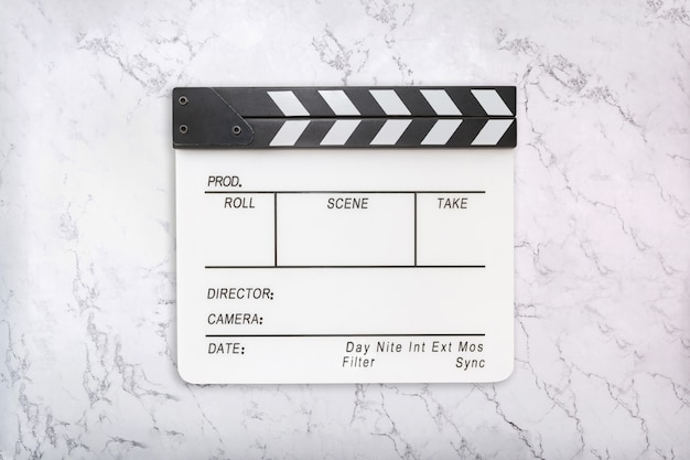 White clapboard on white marble background. flat lay of clapper board on natural marble texture