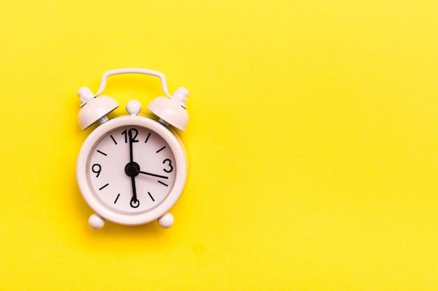 노란색 배경에 흰색 클래식 알람 시계
