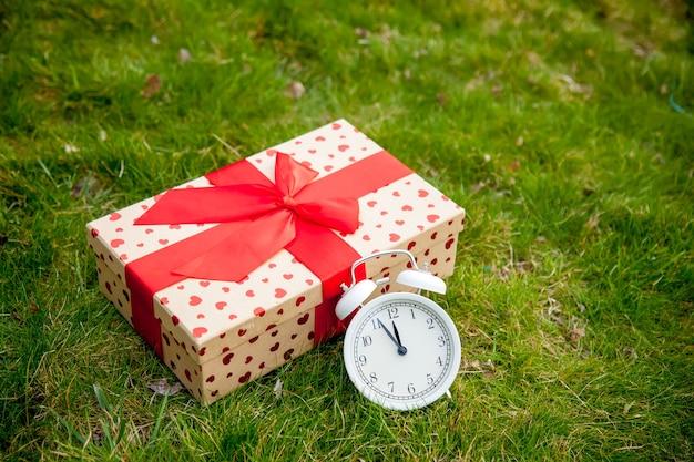 春の緑の草の上の鐘とギフトボックスと白い古典的な目覚まし時計