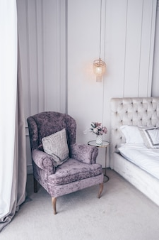 White classic bedroom interior with new year's holiday bouquet in a vase, a gently pink gift present box on the bedside glass table and classic armchair in lavender colors