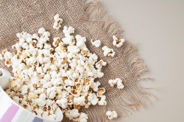 Popcorn classici bianchi su un pezzo di tela da imballaggio.