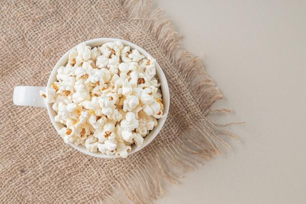 Popcorn classici bianchi in una tazza bianca su un pezzo di tela da imballaggio.