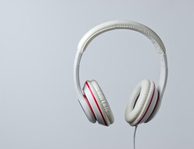 灰色の背景に分離された白い古典的な有線ヘッドフォン。レトロなスタイル。ミニマルミュージックのコンセプト。