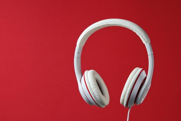 赤い背景で隔離の白い古典的な有線ヘッドフォン。レトロなスタイル。ミニマルミュージックのコンセプト。