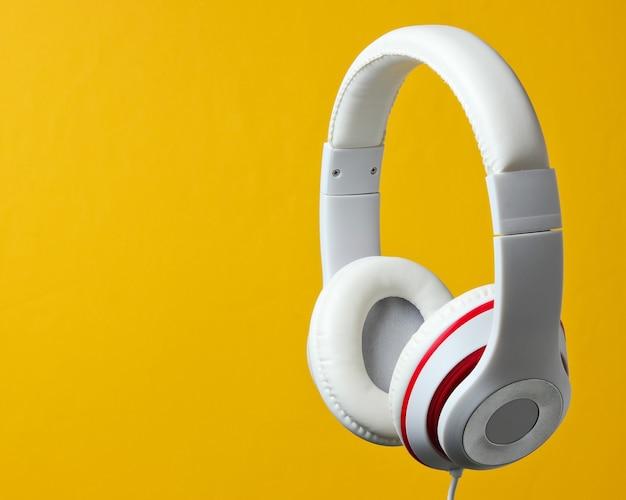黄色の背景に分離された白い古典的な有線ヘッドフォン。レトロなスタイル。ミニマルミュージックのコンセプト。