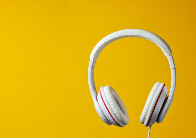 White classic wired headphones isolated on yellow background. retro style. minimalistic music concept.