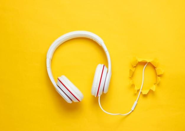 引き裂かれた穴と黄色の背景に白い古典的な有線ヘッドフォン。レトロなスタイル。ミニマルミュージックのコンセプト。