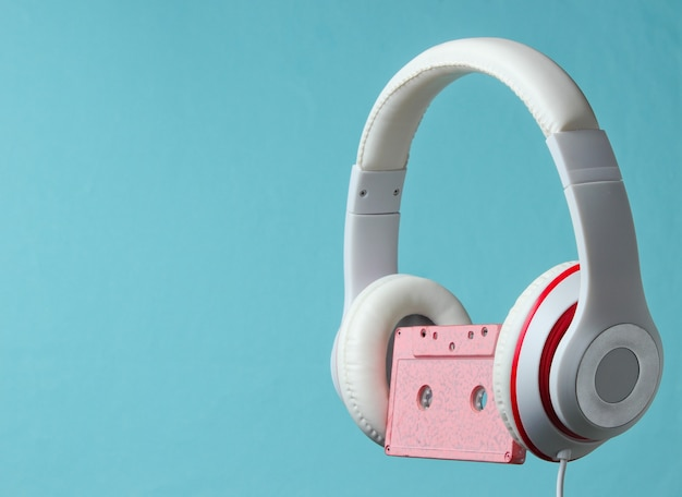 White classic wired headphones with audio cassette isolated on blue background. retro style. 80s. minimalistic music concept.