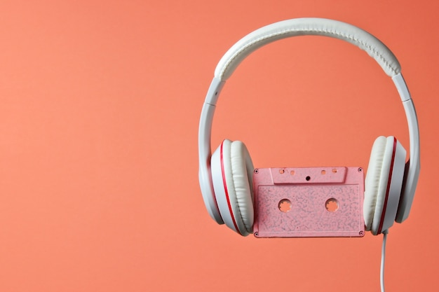 White classic wired headphones with audio cassette isolated on coral color background. retro style. 80s. minimalistic music concept.