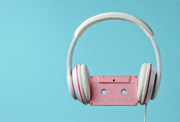 青い背景に分離されたオーディオカセットと白い古典的な有線ヘッドフォン。レトロなスタイル。 80年代。ミニマルミュージックのコンセプト。