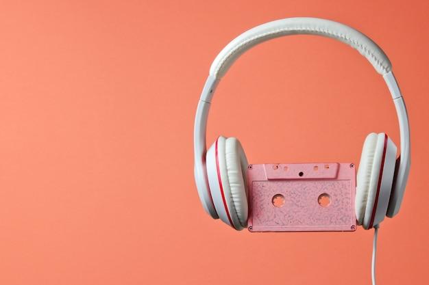 珊瑚色の背景に分離されたオーディオカセット付きの白い古典的な有線ヘッドフォン。レトロなスタイル。 80年代。ミニマルミュージックのコンセプト。