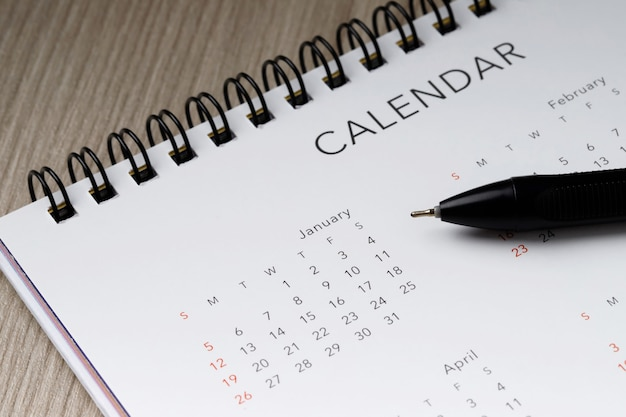 コピースペースと木製の背景に白いきれいなカレンダーとペン