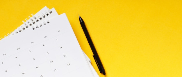 White clean calendar on solid yellow background with copy space, business meeting schedule