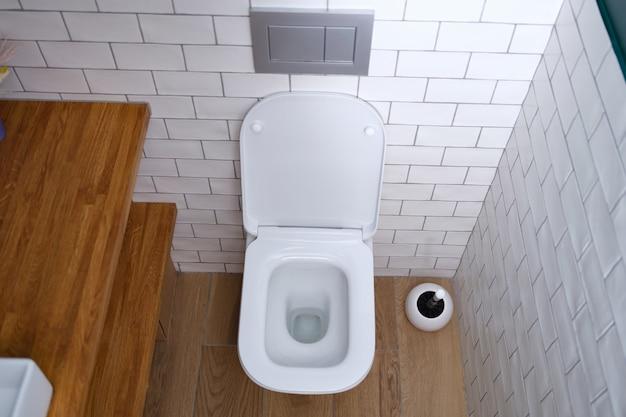 銀の壁ボタンのクローズアップと白いきれいなセラミックトイレ