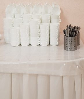 흰색 깨끗한 빈 수프 접시 더미와 테이블 위의 칼붙이, 호텔 카페 서비스