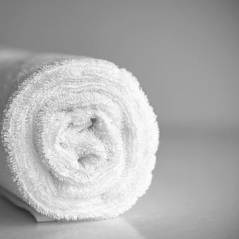 Белое чистое, новое махровое полотенце, скрученное в рулон. чистое белое рулонное текстильное одеяло