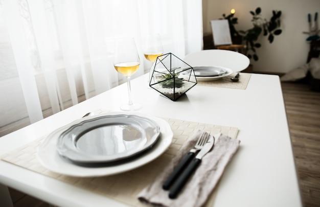 스칸디나비아 스타일의 흰색 로프트 인테리어에 cultery가있는 흰색 깨끗한 접시.