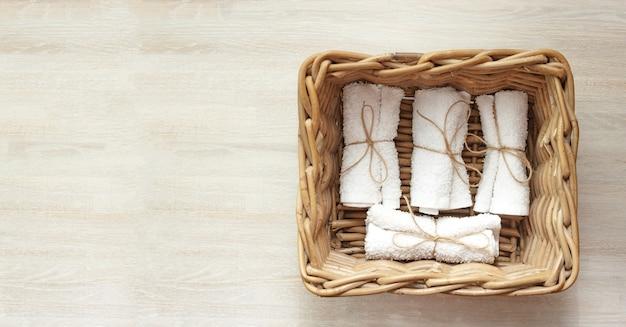 天然木の籐のバスケットに白いきれいなロールテリータオルスタック。閉じる。フラットレイ。選択的なソフトフォーカス。 。テキストコピースペース。